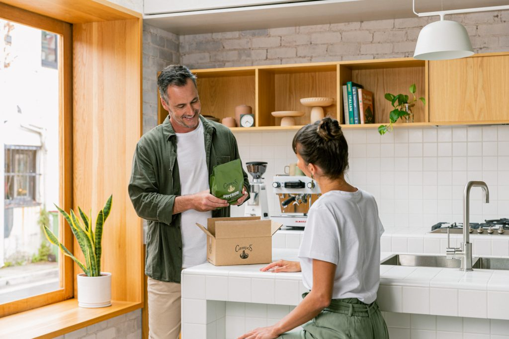 Man and woman in kitchen opening box of coffee